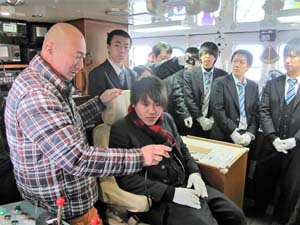 「第三十七八興丸」を見学する水産高校生に漁労機器の扱いなど教える及川漁労長(左)