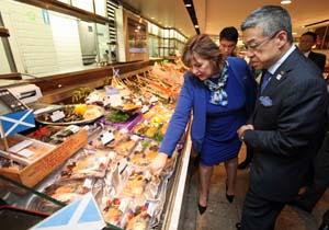 伊勢丹新宿店の水産売り場を視察するヒスロップ大臣(左)に説明する大西社長