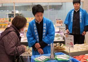 買い物客に答えながら魚を売る男子生徒たち