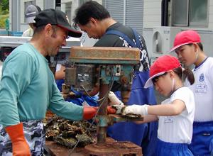 児童らに耳吊り用に貝の殻の穴あけを指導する御野寺部長(左)