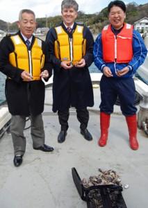室津のカキ養殖を視察するローソン総領事(中央)と中川組合長(左)津田専務(右)。手前が豪州製カキかご