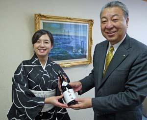 魚に合う日本酒を手渡す藤村さん㊧と、満面の笑顔で受け取る川崎会長