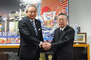 「ともに復興に向けてがんばりましょうと」と握手する菅原市長(左)と白須会長