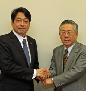 「被災地の本格復興にともにがんばりましょう」と固く握手をする小野寺議員(左)と白須会長
