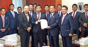 山本大臣(手前中央右)に提言書を手渡す品川部会長(その左)