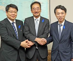 握手を交わす(右から)佐藤前長官、長谷新長官、山口新次長