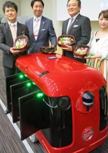 寿司を運ぶキャリロデリバリーを披露する谷口社長(左)と江見社長(その右)