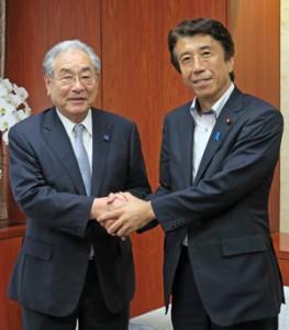 さらなる構造改革を誓い固く握手する齋藤大臣(右)と岸会長