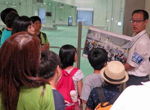 マグロ卸売場の「せり見学台」で都職員から 説明を受ける親子