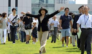 豊洲市場の屋上緑化広場を見学の都民とともに歩く小池知事(中央)