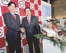 「羽田市場」の野本会長(左)と握手する水留社長