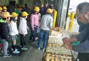行列を作ってカズノコたこ焼きを待つ児童たち