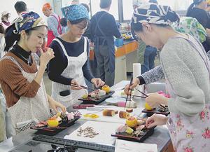完成したおせち料理をプレートに盛り付ける参加者たち