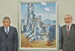 寄贈された油彩画を挟んで記念撮影に納まる八木氏(右)と西川組合長