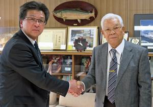 官・業・学一体で時代の水産業の担い手を巣立てようと握手する大井会長(右)と楳原校長