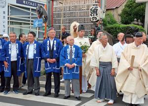 水神社前でみこしの到着を待つ伊藤会長(前列左から4人目)ら築地魚河岸会役員たち
