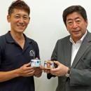 コラボ商品の缶詰を手に業務提携を発表する的埜社長(左)と右田社長