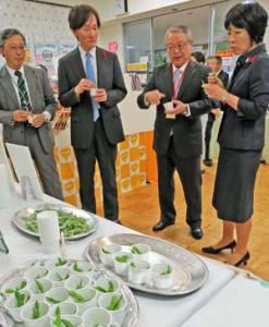 伊藤会長(右から2人目)からマルハニチロの冷凍エダマメ製品 の説明を受ける新井局長(その右)と倉重審議官(左から2人目)。左端は木村専務